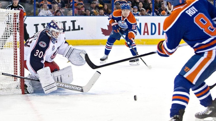 Columbus Blue Jackets' goalie Curtis McElhinney (30) makes the save on Edmonton Oilers' Nail Yakupov (10) and Derek Roy (8) during second period NHL hockey action in Edmonton, Canada on Wednesday March 18, 2015. (AP Photo/The Canadian Press, Jason Franson)