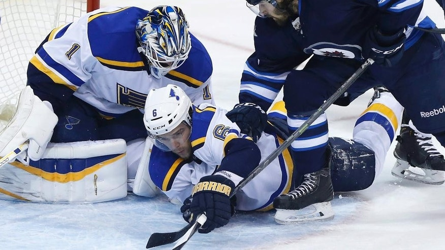 St. Louis Blues goaltender Brian Elliot jumps on the puck as Blues' Zbynek Michalek (6) is pushed to the ice by Winnipeg Jets Eric O'Dell (58) during the first period of an NHL hockey game Thursday, March 19, 2015, in Winnipeg, Manitoba. (AP Photo/The Canadian Press, John Woods)