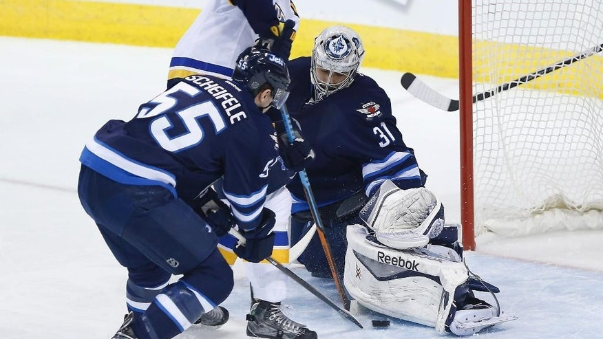 Winnipeg Jets goaltender Ondrej Pavelec (31) stops a shot by St. Louis Blues' Carl Gunnarsson, top, as Jets' Mark Scheifele (55) defends during the first period of an NHL hockey game Thursday, March 19, 2015, in Winnipeg, Manitoba. (AP Photo/The Canadian Press, John Woods)