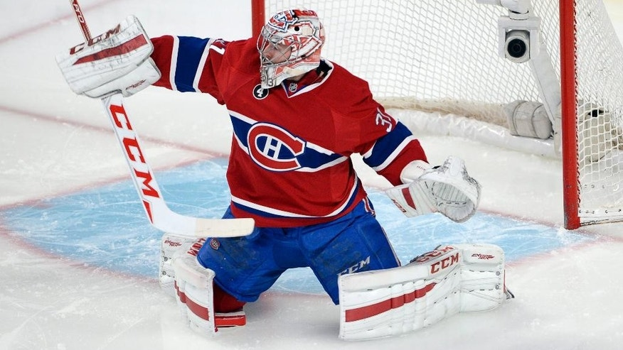 Montreal Canadiens goalie Carey Price (31) makes a save during the first period of an NHL hockey game, Thursday, March 19, 2015 in Montreal. (AP Photo/Canadian Press, Ryan Remiorz)