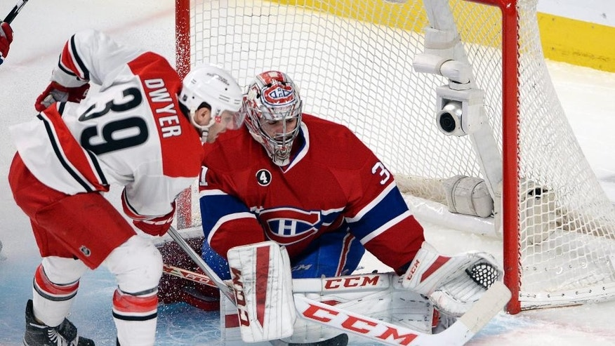 Montreal Canadiens goalie Carey Price (31) makes the save on Carolina Hurricanes right wing Patrick Dwyer (39) during the first period of an NHL hockey game, Thursday, March 19, 2015 in Montreal. (AP Photo/Canadian Press, Ryan Remiorz)