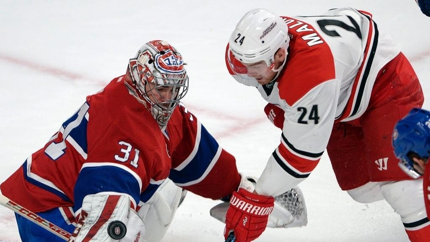 Montreal Canadiens goalie Carey Price (31) makes the save on Carolina Hurricanes center Brad Malone (24) during the second period of an NHL hockey game, Thursday, March 19, 2015 in Montreal. (AP Photo/Canadian Press, Ryan Remiorz)