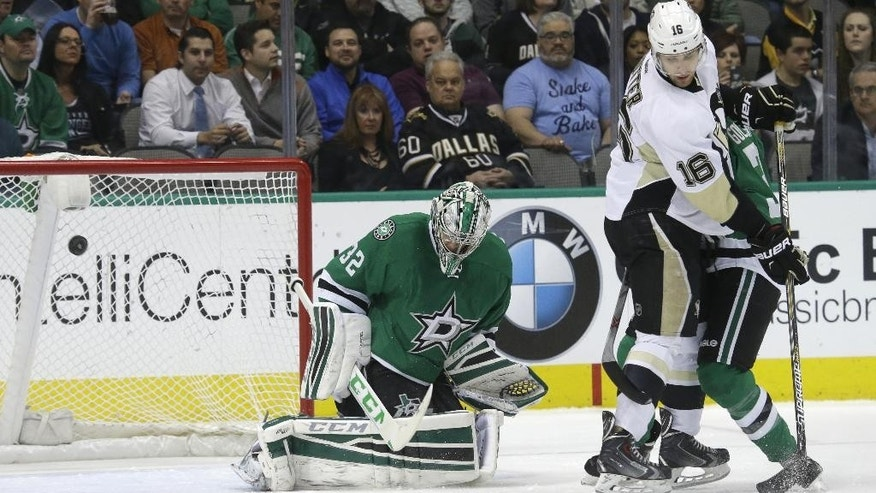 The shoot goes wide as Dallas Stars goalie Kari Lehtonen (32) and Alex Goligoski (33) defend the goal against Pittsburgh Penguins center Brandon Sutter (16) during the first period of an NHL hockey game Thursday, March 19, 2015, in Dallas. (AP Photo/LM Otero)