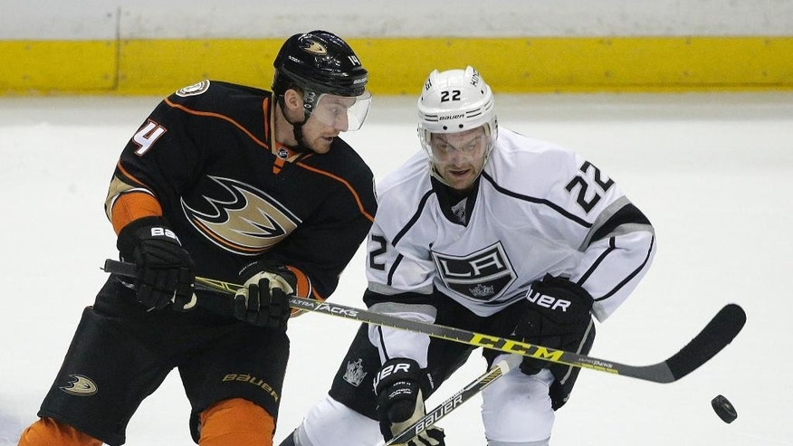 Anaheim Ducks' Rene Bourque, left, and Los Angeles Kings' Trevor Lewis fight for the puck during the first period of an NHL hockey game, Wednesday, March 18, 2015, in Anaheim, Calif. (AP Photo/Jae C. Hong)