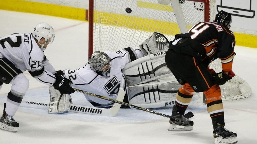 Los Angeles Kings goalie Jonathan Quick, center, stops a shot by Anaheim Ducks' Tomas Fleischmann, right, of the Czech Republic, as Kings' Trevor Lewis puts pressure on Fleischmann during the first period of an NHL hockey game, Wednesday, March 18, 2015, in Anaheim, Calif. (AP Photo/Jae C. Hong)