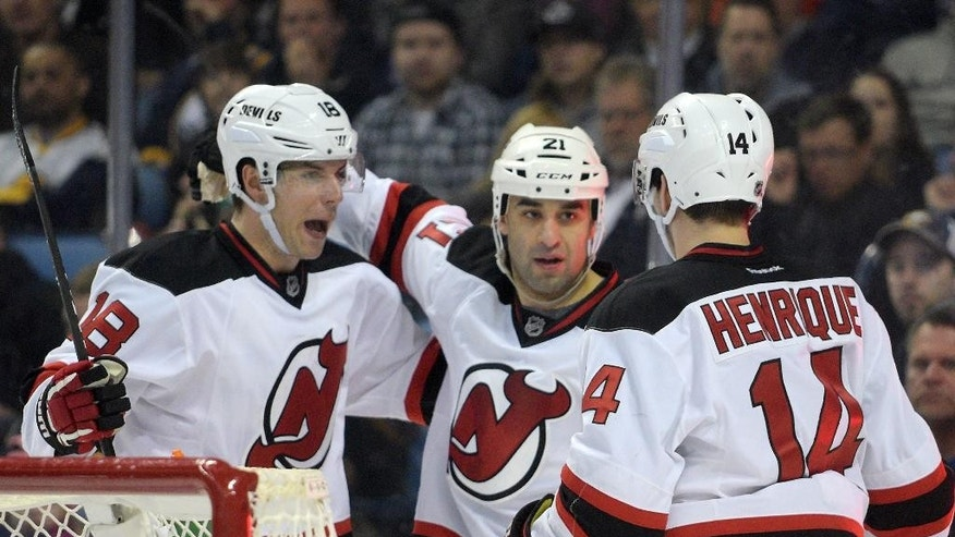 New Jersey Devils Steve Bernier (18) Scott Gomez (21) and Adam Henrique (14) celebrate the first of two goals by Bernier during the second period of an NHL hockey game against the Buffalo Sabres Friday, March 20, 2015, in Buffalo, N.Y. (AP Photo/Gary Wiepert)