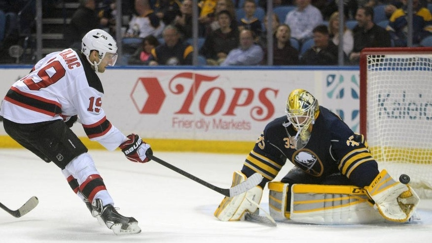 New Jersey Devils center Travis Zajac (19) shoots on Buffalo Sabres goaltender Anders Lindback (35), of Sweden, during the second period of an NHL hockey game Friday, March 20, 2015, in Buffalo, N.Y. (AP Photo/Gary Wiepert)