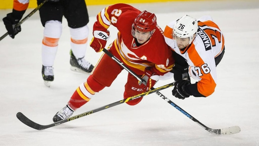 Philadelphia Flyers Chris Vandevelde, right, and Calgary Flames Jiri Hudler, from the Czech Republic, dive for the puck during third period of an NHL hockey game in Calgary, Alberta, Thursday, March 19, 2015. (AP Photo/The Canadian Press, Jeff McIntosh)