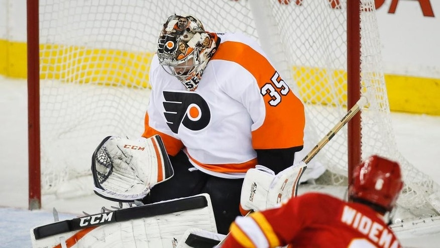 Philadelphia Flyers goalie Steve Mason, right, lets in a goal by Calgary Flames Dennis Wideman during the second period of an NHL hockey game, Thursday, March 19, 2015 in Calgary, Alberta. (AP Photo/Canadian Press, Jeff McIntosh)