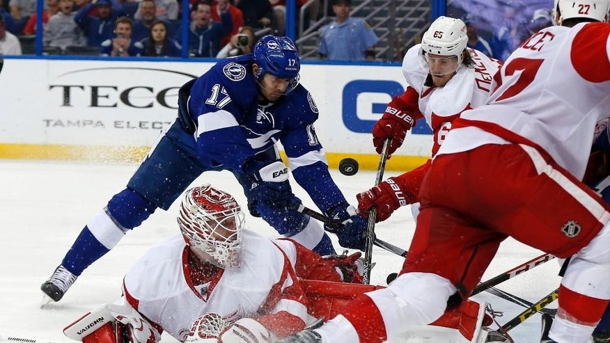 Detroit Red Wings goalie Jimmy Howard, bottom left, looks back for a rebound as Red Wings defenseman Danny DeKeyser (65) and Tampa Bay Lightning's Alex Killorn reach for it during the second period of an NHL hockey game Friday, March 20, 2015, in Tampa, Fla. (AP Photo/Mike Carlson)