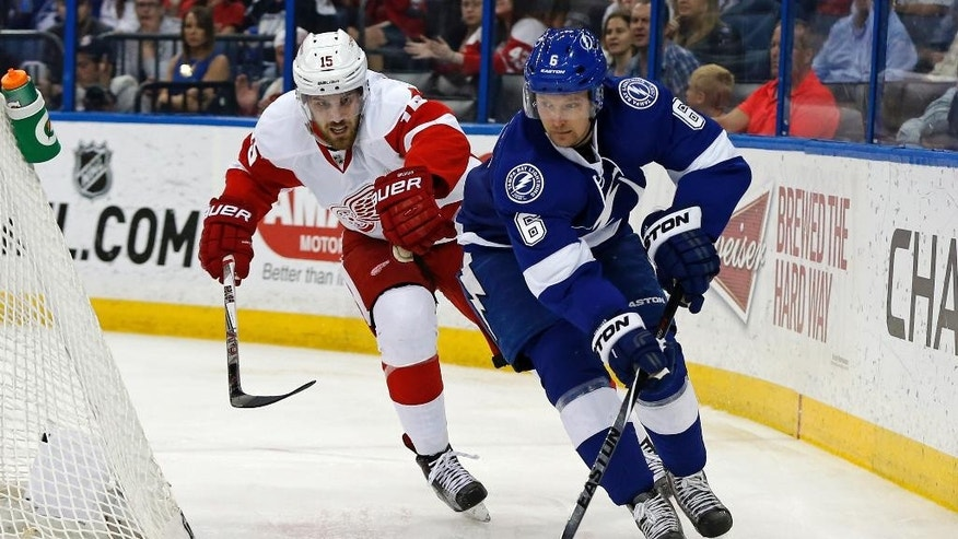 Tampa Bay Lightning's Anton Stralman, of Sweden, avoids the check of Detroit Red Wings' Riley Sheahan during the second period of an NHL hockey game Friday, March 20, 2015, in Tampa, Fla. (AP Photo/Mike Carlson)