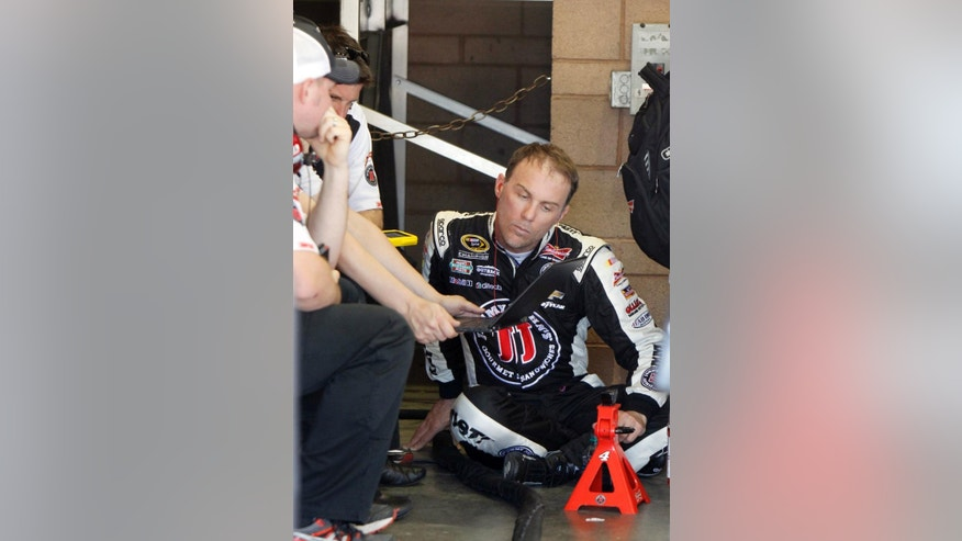 Driver Kevin Harvick, right, talks with his crew in the garage during a practice session to qualify for Sunday's NASCAR Sprint Cup Series auto race in Fontana, Calif., Friday, March 20, 2015. (AP Photo/Alex Gallardo)