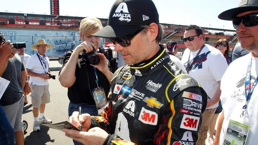 Driver Jeff Gordon, center, signs an autograph for a fan after a practice session to qualify for Sunday's NASCAR Sprint Cup Series auto race in Fontana, Calif., Friday, March 20, 2015. (AP Photo/Alex Gallardo)