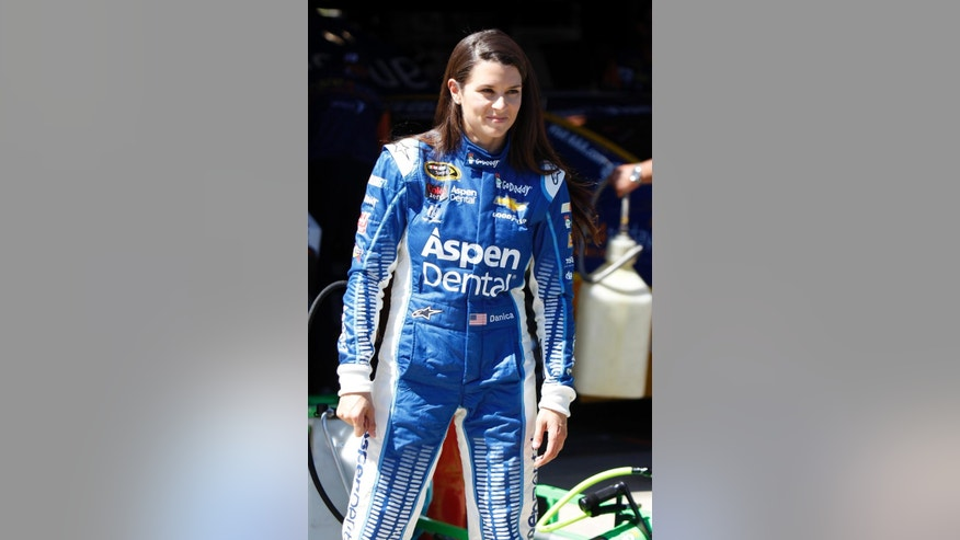 Driver Danica Patrick walks in the garage area after a practice session to qualify for Sunday's NASCAR Sprint Cup Series auto race in Fontana, Calif., Friday, March 20, 2015. (AP Photo/Alex Gallardo)
