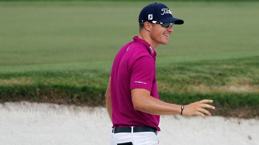Morgan Hoffmann acknowledges the crowd after hitting out of a bunker and into the hole for an eagle on the sixth green during first round of the Arnold Palmer Invitational golf tournament in Orlando, Fla., Thursday, March 19, 2015.(AP Photo/Reinhold Matay)