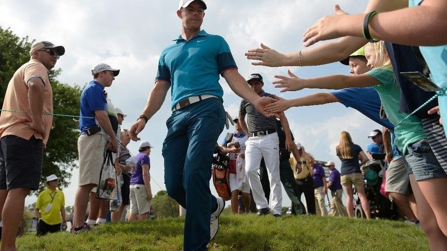 Rory McIlroy, center, of Northern Ireland, slaps hands with young fans, while walking to the 14th tee, during first round of the Arnold Palmer Invitational golf tournament in Orlando, Fla., Thursday, March 19, 2015.(AP Photo/Phelan M. Ebenhack)