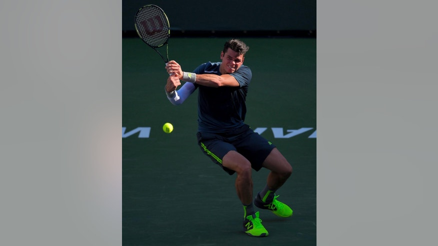 Milos Raonic, of Canada, returns a volley from Rafael Nadal, of Spain, during their match at the BNP Paribas Open tennis tournament, Friday, March 20, 2015 in Indian Wells, Calif. (AP Photo/Mark J. Terrill)