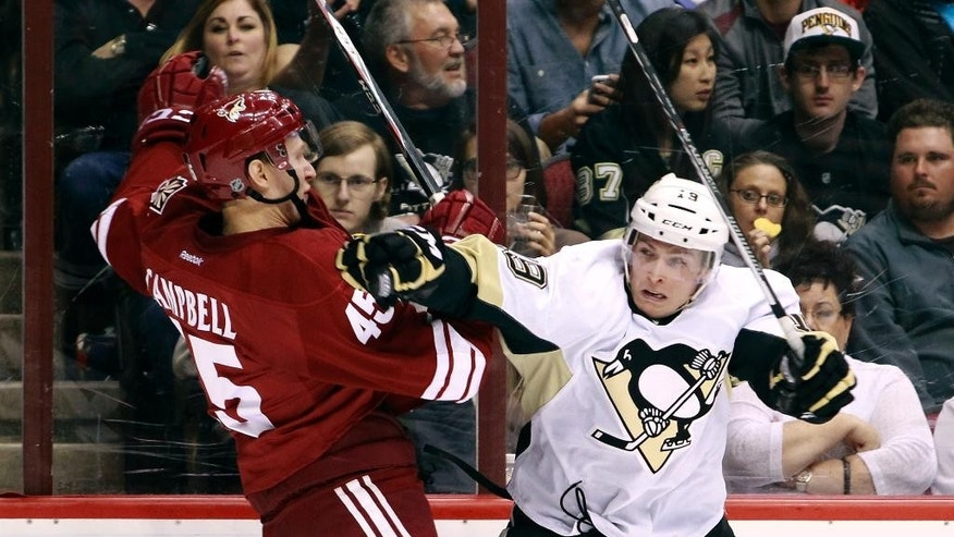 Arizona Coyotes' Andrew Campbell, left, is checked by Pittsburgh Penguins' Beau Bennett (19) during the second period of an NHL hockey game, Saturday, March  21, 2015, in Glendale, Ariz. (AP Photo/Ralph Freso)