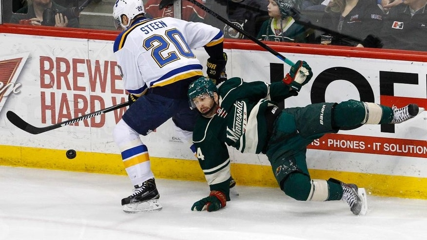 Minnesota Wild right wing Justin Fontaine, right, falls while chasing the puck with St. Louis Blues left wing Alexander Steen (20) during the first period of an NHL hockey game in St. Paul, Minn., Saturday, March 21, 2015. (AP Photo/Ann Heisenfelt)