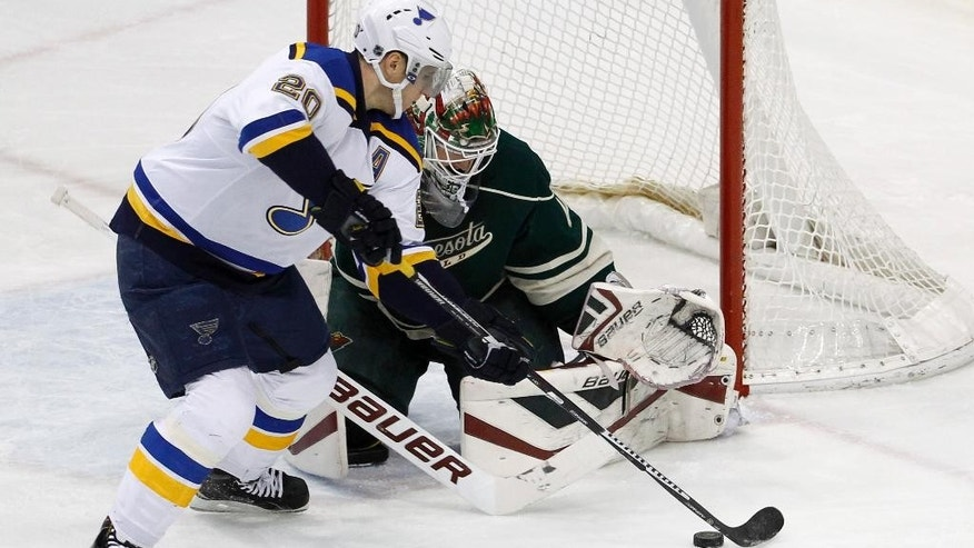 St. Louis Blues left wing Alexander Steen (20) reaches for the deflected puck in front of Minnesota Wild goalie Devan Dubnyk, right, during the first period of an NHL hockey game in St. Paul, Minn., Saturday, March 21, 2015. (AP Photo/Ann Heisenfelt)