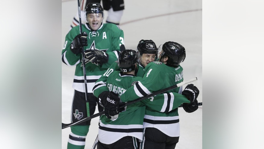 Dallas Stars center Shawn Horcoff (10) celebrates scoring a goal with teammates Jason Demers (4), Alex Goligoski (33) and Vernon Fiddler (38) during the third period of an NHL hockey game against the Chicago Blackhawks Saturday, March 21, 2015, in Dallas. The Stars won 4-0. (AP Photo/LM Otero)