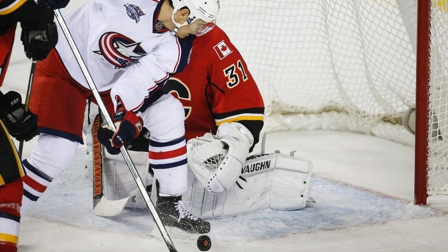 Columbus Blue Jackets Rene Bourque, left, scores the game-winning goal on Calgary Flames goalie Karri Ramo, from Finland, during overtime in an NHL hockey game, Saturday, March 21, 2015 in Calgary, Alberta. (AP Photo/The Canadian Press, Jeff McIntosh)