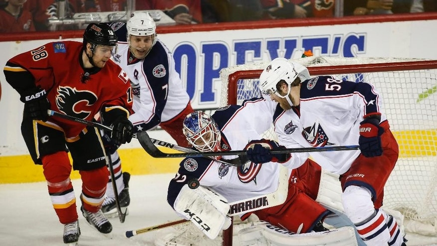 Columbus Blue Jackets goalie Sergei Bobrovsky, center, from Russia, scrambles for the puck while teammates David Savard, right, and Jack Johnson, second from left, try to help as Calgary Flames Matt Stajan closes in during the second period of an NHL hockey game, Saturday, March 21, 2015 in Calgary, Alberta. (AP Photo/The Canadian Press, Jeff McIntosh)