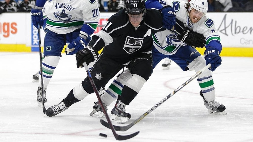 Los Angeles Kings' Anze Kopitar, left, of Slovenia, and Vancouver Canucks' Chris Tanev fight for the puck during the second period of an NHL hockey game, Saturday, March 21, 2015, in Los Angeles. (AP Photo/Jae C. Hong)