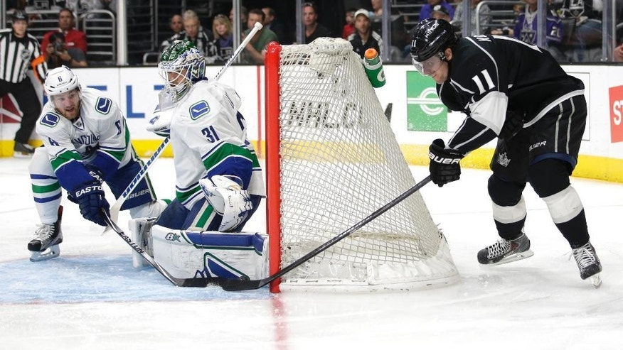 Los Angeles Kings' Anze Kopitar, right, of Slovenia, tries to score against Vancouver Canucks goalie Eddie Lack, of Sweden, during the second period of an NHL hockey game, Saturday, March 21, 2015, in Los Angeles. (AP Photo/Jae C. Hong)