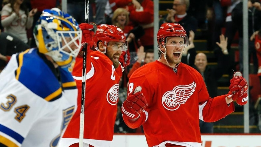 Detroit Red Wings' Justin Abdelkader, right, celebrates with teammate Henrik Zetterberg, center, after scoring against St. Louis Blues goalie Jake Allen (34) in overtime of an NHL hockey game in Detroit, Sunday, March 22, 2015. Detroit won 2-1. (AP Photo/Paul Sancya)