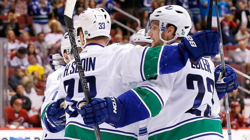 Vancouver Canucks' Alexander Edler (23), of Sweden, celebrates his goal against the Arizona Coyotes with teammates, including Henrik Sedin (33), of Sweden, during the third period of an NHL hockey game Sunday, March 22, 2015, in Glendale, Ariz. The Canucks defeated the Coyotes 3-1. (AP Photo/Ross D. Franklin)