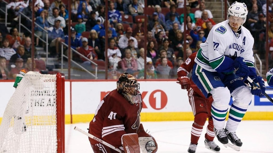 Vancouver Canucks' Daniel Sedin (22), of Sweden, jumps out of the way on a shot by Canucks' Alexander Edler as he scores against Arizona Coyotes' Mike Smith (41) during the third period of an NHL hockey game Sunday, March 22, 2015, in Glendale, Ariz.  The Canucks defeated the Coyotes 3-1. (AP Photo/Ross D. Franklin)