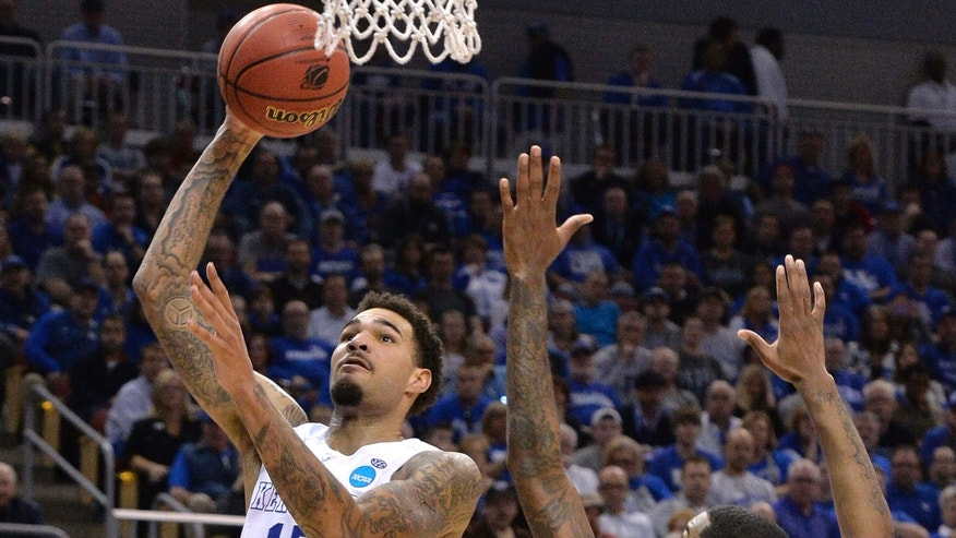 March 21, 2015: Kentucky's Willie Cauley-Stein, left, goes up for a shot past the defense of Cincinnati's Octavius Ellis during the second half of an NCAA tournament college basketball game.