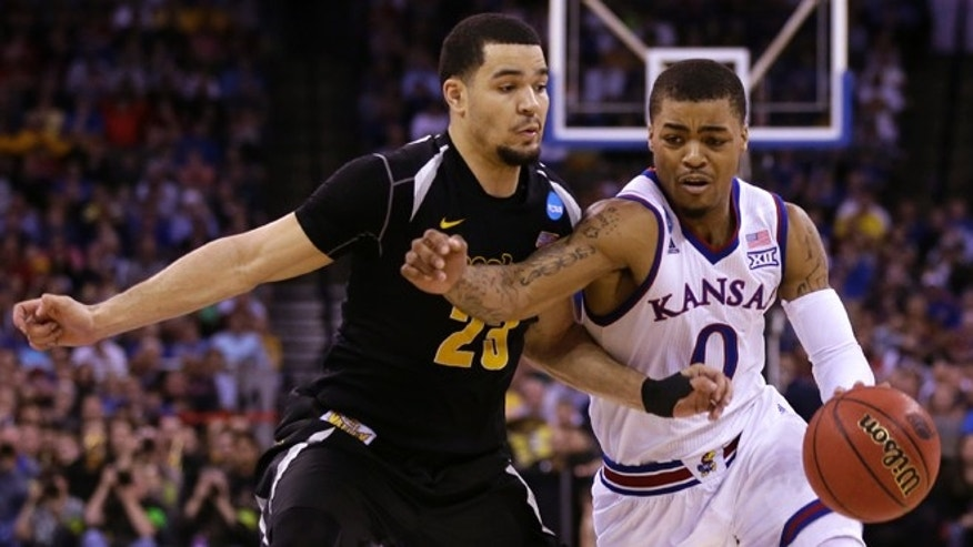March 22, 2015: Kansas guard Frank Mason III tries to drive past Wichita State guard Fred VanVleet, left, during the second half of an NCAA college basketball tournament Round of 32 game in Omaha, Neb.