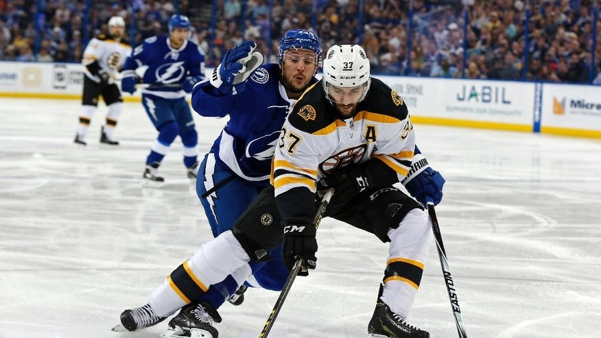 Boston Bruins' Patrice Bergeron avoids a check from Tampa Bay Lightning's Ryan Callahan during the first period of an NHL hockey game Sunday, March 22, 2015, in Tampa, Fla. (AP Photo/Mike Carlson)