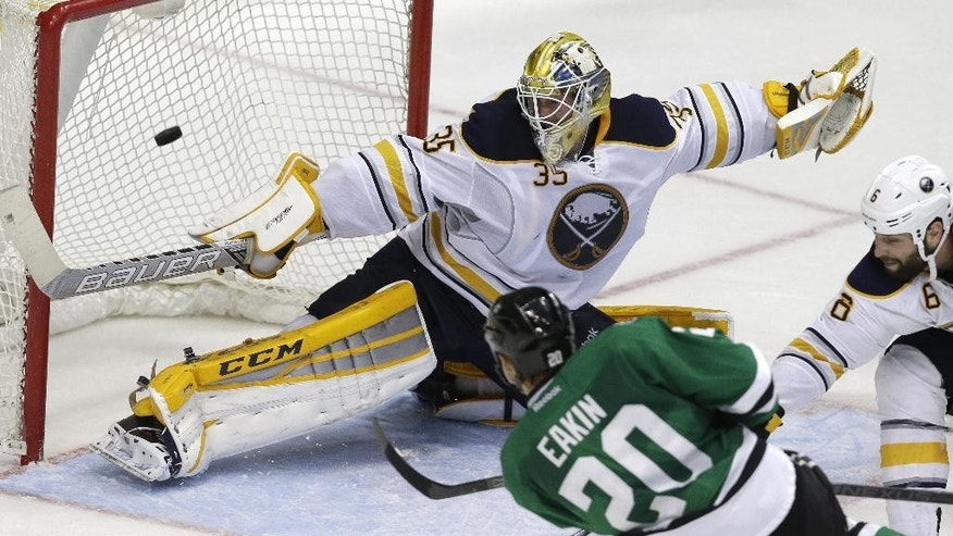 Dallas Stars center Cody Eakin (20) scores a goal against Buffalo Sabres goalie Anders Lindback (35) and defenseman Mike Weber (6) during the third period of an NHL hockey game Monday, March 23, 2015, in Dallas. The Stars won 4-3. (AP Photo/LM Otero)