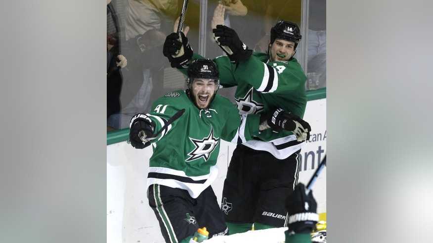 Dallas Stars center Tyler Seguin (91) and  left wing Jamie Benn (14) celebrate a goal scored by teammate Shawn Horcoff, not shown, during the third period of an NHL hockey game against the Buffalo Sabres Monday, March 23, 2015, in Dallas. The Stars won 4-3. (AP Photo/LM Otero)