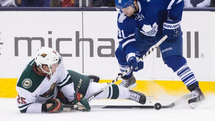 Toronto Maple Leafs' Phil Kessel, right, battles for the puck with Minnesota Wild's Jonas Brodin during second period NHL hockey action in Toronto on Monday, March 23, 2015. (AP Photo/The Canadian Press, Chris Young)