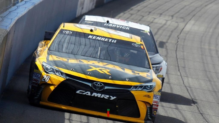 Matt Kenseth races in front of Kevin Harvick during a NASCAR Sprint Cup Series auto race in Fontana, Calif., Sunday, March 22, 2015. (AP Photo/Alex Gallardo)
