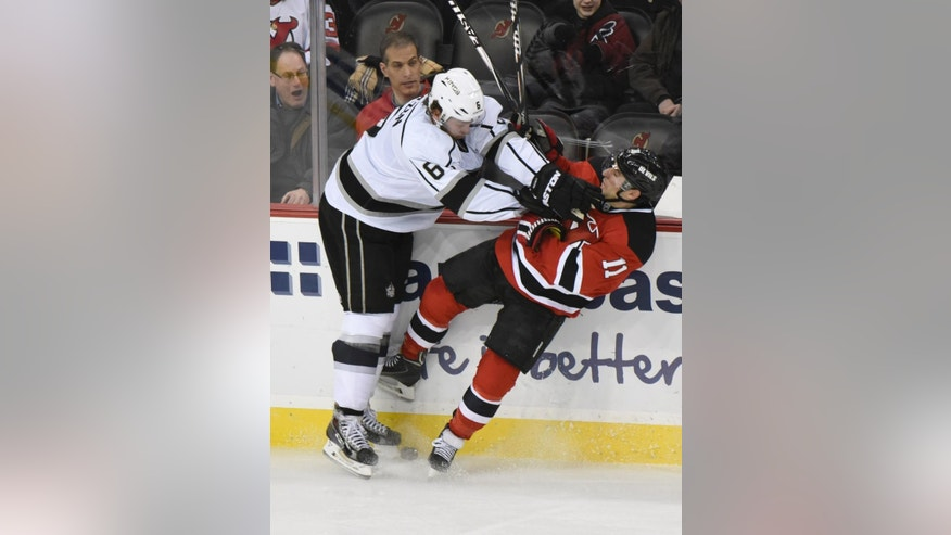 Los Angeles Kings' Jake Muzzin, left, checks New Jersey Devils' Stephen Gionta during the second period of an NHL hockey game Monday, March 23, 2015, in Newark, N.J. (AP Photo/Bill Kostroun)