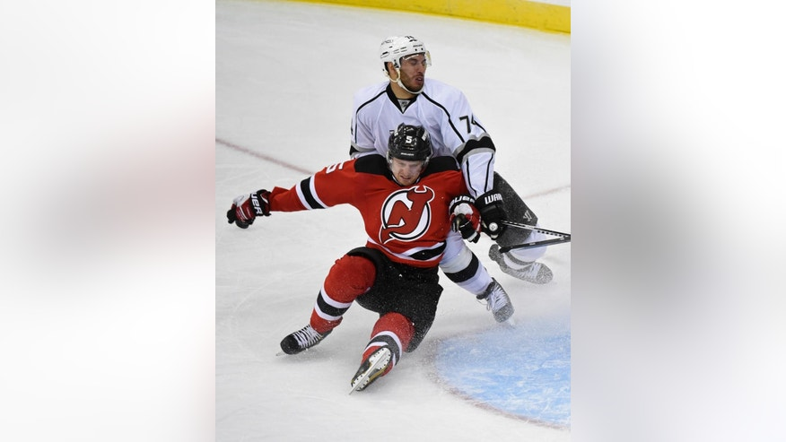 Los Angeles Kings' Dwight King (74) checks New Jersey Devils' Adam Larsson during the second period of an NHL hockey game Monday, March 23, 2015, in Newark, N.J. (AP Photo/Bill Kostroun)