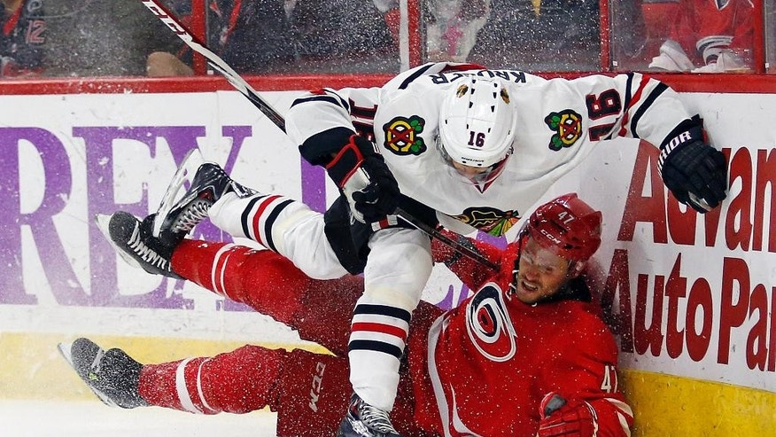 Chicago Blackhawks' Marcus Kruger (16) collides with Carolina Hurricanes' Michal Jordan (47), of the Czech Republic, during the first period of an NHL hockey game Monday, March 23, 2015, in Raleigh, N.C. (AP Photo/Karl B DeBlaker)