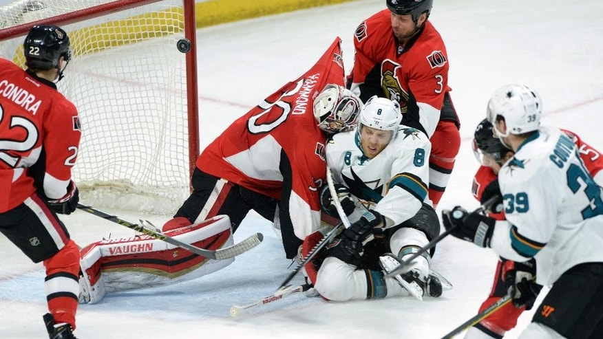 San Jose Sharks' Joe Pavelski (8) slams into Ottawa Senators goalie Andrew Hammond as his shot makes its way into the net for a second period goal during an NHL hockey game in Ottawa, Ontario, Monday, March 23, 2015. (AP Photo/The Canadian Press, Sean Kilpatrick)