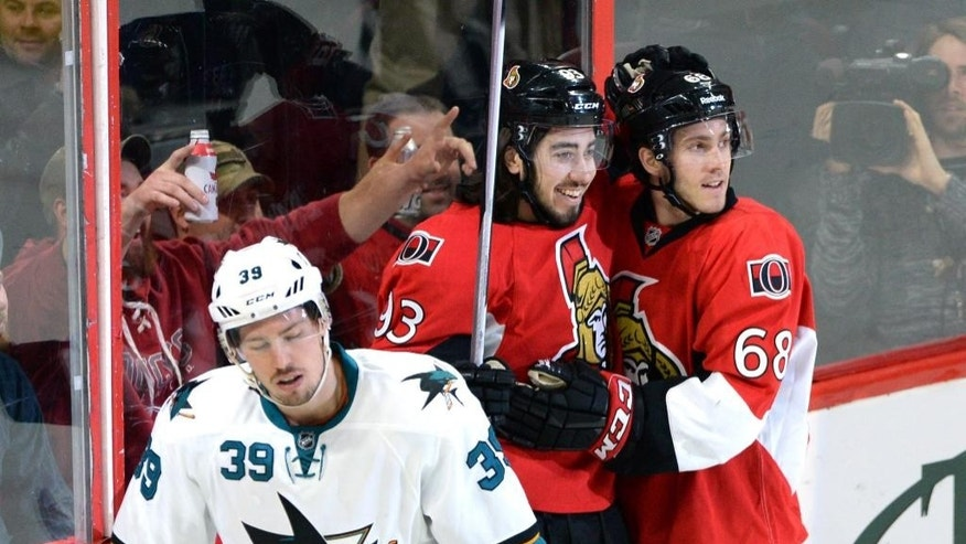 Ottawa Senators' Mika Zibanejad, center, celebrates a goal with teammate Mike Hoffman as San Jose Sharks' Logan Couture (39) skates away during the first period of an NHL hockey game Monday, March 23, 2015, in Ottawa, Ontario. (AP Photo/The Canadian Press, Sean Kilpatrick)