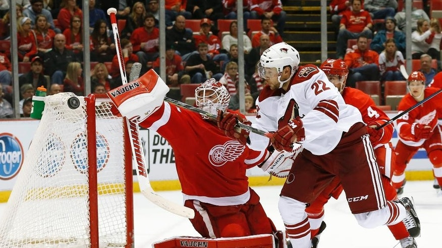 Detroit Red Wings goalie Jimmy Howard (35) deflects a shot by Arizona Coyotes left wing Craig Cunningham (22) during the third period of an NHL hockey game in Detroit on Tuesday, March 24, 2015. Arizona won 5-4 in a shootout. (AP Photo/Paul Sancya)