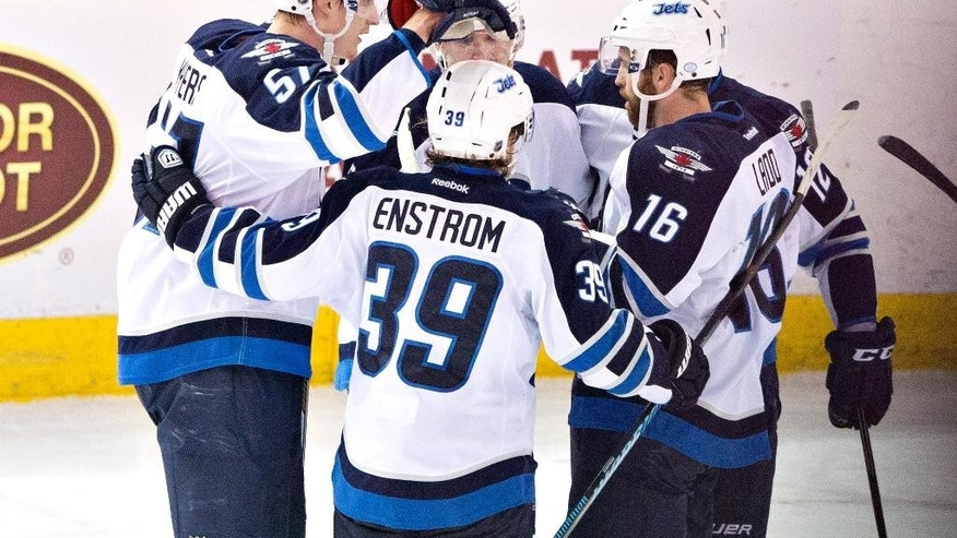 Winnipeg Jets' Tyler Myers (57), Toby Enstrom (39) and Andrew Ladd (16) celebrate a goal with teammates against the Edmonton Oilers during the second period of an NHL hockey game Monday, March 23, 2015, in Edmonton, Alberta. (AP Photo/The Canadian Press, Jason Franson)