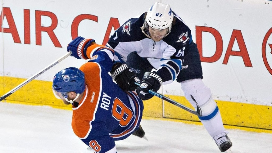 Winnipeg Jets' Michael Frolik (67) checks Edmonton Oilers' Derek Roy (8) during the second period of an NHL hockey game Monday, March 23, 2015, in Edmonton, Alberta. (AP Photo/The Canadian Press, Jason Franson)