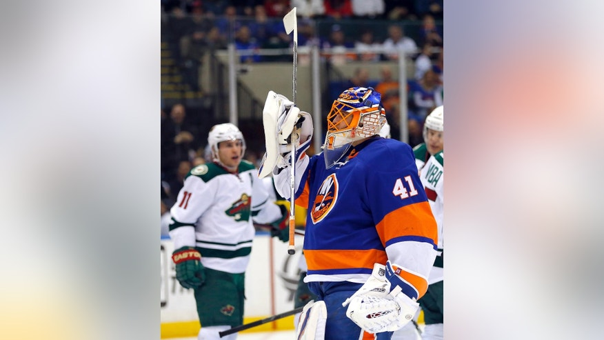 New York Islanders goalie Jaroslav Halak (41) looks up as Minnesota Wild left wing Zach Parise (11) celebrates scoring a goal to tie the score during the third period of an NHL hockey game Tuesday, March 24, 2015, in Uniondale, N.Y.  Minnesota won 2-1 in a shootout. (AP Photo/Paul Bereswill)