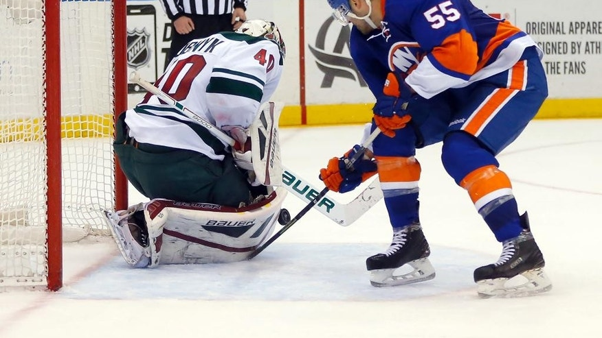Minnesota Wild goalie Devan Dubnyk (40) stops a shot on a breakaway by New York Islanders defenseman Johnny Boychuk (55) during overtime in an NHL hockey game Tuesday, March 24, 2015, in Uniondale, N.Y. Minnesota won 2-1 in a shootout. (AP Photo/Paul Bereswill)