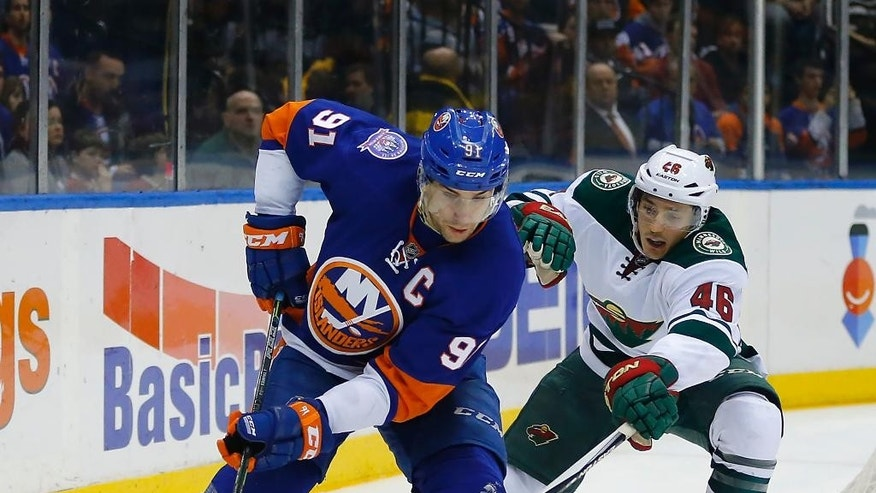 New York Islanders center John Tavares (91) skates around Minnesota Wild defenseman Jared Spurgeon (46) during the second period of an NHL hockey game against the Minnesota Wild Tuesday, March 24, 2015, in Uniondale, N.Y.  (AP Photo/Paul Bereswill)
